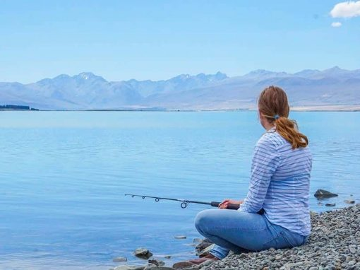 A guest at Isolation Bay fishing on the property's private Lake Tekapo beach.