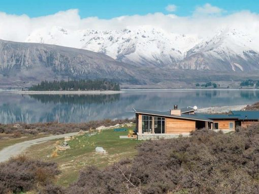 The landscape surrounding Isolation Bay includes famous Lake Tekapo and the mountains of the Southern Alps.